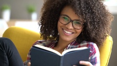 Mixed-race girl with eyeglasses reading book at home Stock Footage
