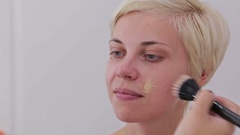 Close up shot. Makeup artist applying liquid tonal foundation on the face Stock Footage