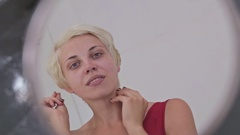 Sensual woman without make-up looking at her reflection in mirror, fixing hair Stock Footage