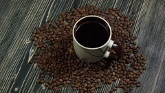 Drop falling into a cup of coffee. On a wooden background Stock Footage