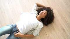 Upper view of woman laying on the back on wooden floor Stock Footage