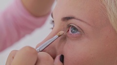 Professional make-up artist applying cream base eyeshadow primer to model eye Stock Footage