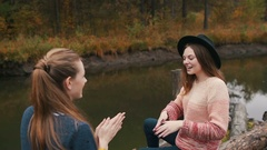 Two friends play hand-clapping game. On the logs. Autumn forest Stock Footage
