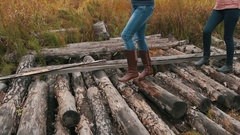 Two young girls in autumn wood walk on logs Stock Footage