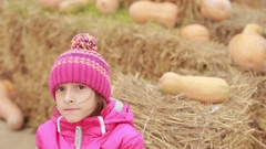 Little girl sitting on the hay, decorated pumpkins, waiting for holiday Stock Footage
