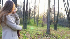 Mother with baby spinning around. Walking outdoor at autumn park Stock Footage