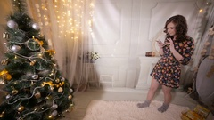 Attractive girl send and recieve text message near Christmas tree during New Stock Footage