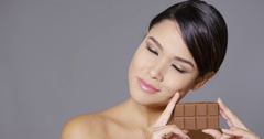 Sensual young woman nibbling on a chocolate bar Stock Footage