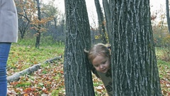 Mother with baby playing hide-and-seek outdoor, looking through the trees Stock Footage