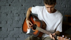 Attractive young man playing guitar at home Stock Footage