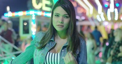 Young woman daydreaming at a funfair Stock Footage