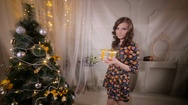 Attractive young woman gives golden gift ribbon box into camera Stock Footage