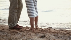 Close-up of legs of young couple on a sandy beach. The girl comes into water Stock Footage