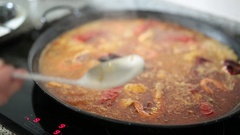 Paella cooking on an electric stove Stock Footage