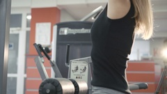 Woman working out with simulator for muscles on arms and back in the gym in 4k Stock Footage