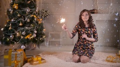 Beautiful girl near christmas tree holding sparkler, bengal fire. Celebrating Stock Footage