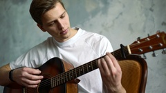 Young attractive male plays acoustic guitar, indoor shoot Stock Footage