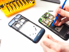 Technician disassebmling mobile phone Stock Footage