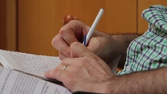 Man writes notes in notebook as he listens to lecture - Close Up Stock Footage