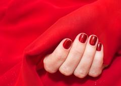 Female hands with red manicure with glittering sparkles at red fabric Stock Photos