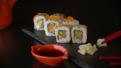 Hand with red chopsticks taking roll sushi from dark plate Stock Footage