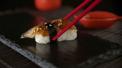Eating sushi roll using red chopsticks Stock Footage