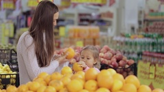 Mother and baby daughter in supermarket buying fruits and vegetables Stock Footage