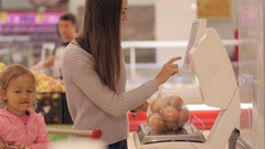 Young mother with little daugher weighting vegetables and fruits in supermarket Stock Footage