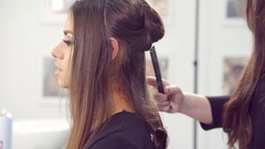 Attractive young woman having her hair styled by a hairdresser Stock Footage