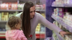 Woman with daughter picking fresh dairy products in refrigerated section Stock Footage
