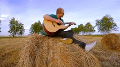 Pretty young woman playing guitar, sitting against a hay roll Stock Footage