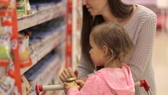 Young mother with baby daughter shopping in supermarket Stock Footage