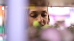 Young woman choosing flowers in flowers section of supermarket. Stock Footage