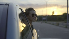 The beautiful girl outside of the window in motion of car. Slow motion Arkistovideo