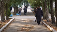 Many senior people walking along alley, life after retirement, health insurance Stock Footage