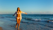 Young woman walking on beach Stock Footage