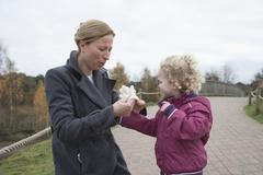 Mother putting glove on daughter's hand (4-5) Stock Photos