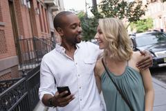 Smiling couple walking in residential district Stock Photos
