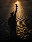 USA, New York State, New York City, Silhouette of Statue of Liberty at sunrise Kuvituskuvat