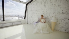 Cute young blonde woman in wedding dress posing in studio with huge ice cream Stock Footage