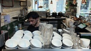 Man arranging cups in coffee shop Stock Footage