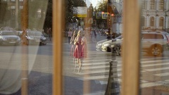 Cute young blonde woman in red dress crossing road in reflection Stock Footage