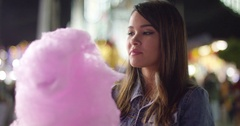 Laughing young woman eating pink candy floss Stock Footage