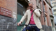 Man on bicycle talking on phone Stock Footage