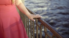 Cute young blonde woman in red dress walking on embankment Stock Footage