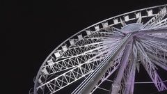 Ferris wheel and rollercoaster in motion at amusement park at night Stock Footage