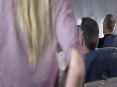 Young man helps woman stow carry on bag in main cabin of airliner 4K Stock Footage