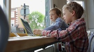 Brothers playing on laptop Stock Footage