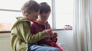 Brothers playing on smartphone Stock Footage