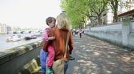 Mother with sons walking by river Stock Footage